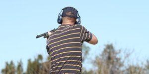 man shooting shotgun